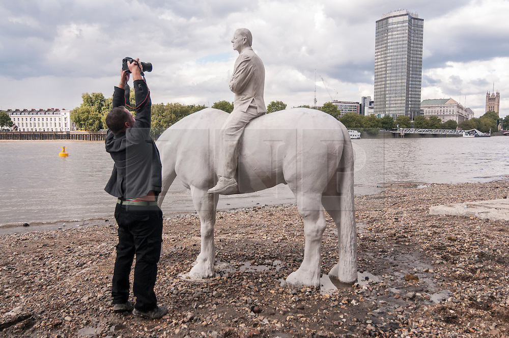 "© Licensed to London News Pictures. 02/09/2015 London, UK. The art installation entitled ""The Rising Tide"" (comprising four horse-riders on horses with petroleum pumps for heads) by the underwater eco-sculptor Jason deCaires Taylor (pictured taking a photo), which stands on the foreshore of the River Thames in Vauxhall and is revealed with each low tide.  The installation aims to question man's reliance on fossil fuels and is part of this year's Totally Thames festival. Photo credit : Stephen Chung/LNP"