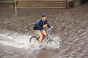 A cyclist rides through floodwaters in the historic Battery as Hurricane Joaquin brings heavy rain, flooding and strong winds as it passes offshore October 3, 2015 in Charleston, South Carolina.