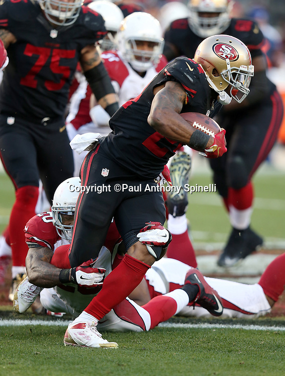 San Francisco 49ers running back Shaun Draughn (24) gets tackled by Arizona Cardinals strong safety Deone Bucannon (20) for a loss of 6 yards on a fourth quarter running play during the 2015 week 12 regular season NFL football game against the Arizona Cardinals on Sunday, Nov. 29, 2015 in Santa Clara, Calif. The Cardinals won the game 19-13. (©Paul Anthony Spinelli)