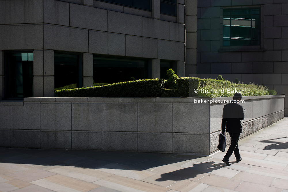 A businessman checks messages while walking past an urban garden of bushes and shrubs.