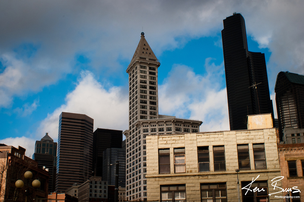 Smith Tower & Bank of America Tower dominate Seattle Skyline with a stormy sky above them.