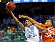 North Carolina's Italee Lucas is fouled by Clemson's Sthefany Thomas as she drives to the basket as North Carolina defeats Clemson 78 - 64 in the 2011 ACC Women's Basketball Tournament held at the Greensboro Coliseum in Greensboro, North Carolina.  (Photo by Mark W. Sutton)
