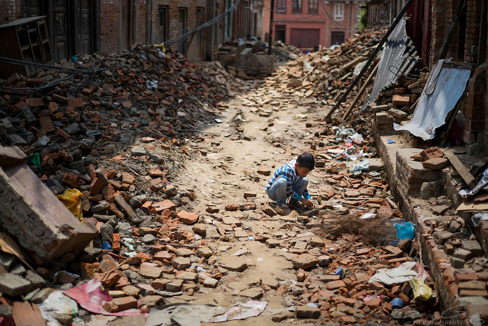A boy searches through the rubble of buildings destroyed by the 2015 Nepal earthquake.