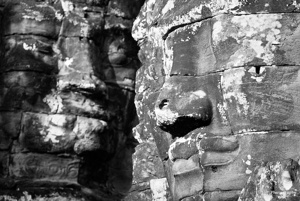 Two smiling stone faces of the bodhisattva Avalokiteshvara at The Bayon temple in the walled city of Angkor Thom, Siem Reap, Cambodia