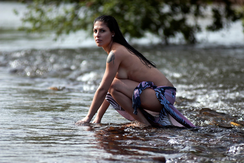 A beautiful topless girl with long black hair, wearing a blue patterned sarong crouches  in the ripples of a shallow fast flowing river.