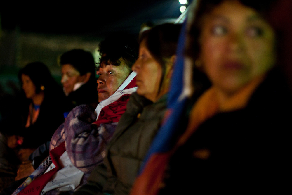 """Elizabet Segovia, sister of Darío Segovia, one of the 33 miners trapped, holds a flag during a mass at """"Camp Hope"""". From August 5th, 33 miners are trapped after a cave-in at San Jose Mine in the north of Chile. 17 days after these miners were discovered, alive. More of two months after they will be rescue. All this time some families stay out side the mine borders waiting for news and theses parents, the past of the days gives place a little town knows as """"Camp Hope""""."""