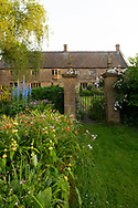 Herbaceous borders of Delphinium Pacific hybrid, Hemerocallis and Phlomisrusseliana at Lower Severalls Farmhouse,  Crewkerne, Somerset, UK