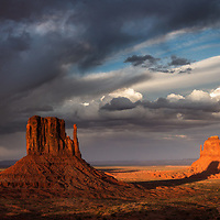After two days of waiting, a strong storm clears just before the sun dips under the horizon and its light blazes across Monument Valley just for a moment. A full moon appears from the clouds.