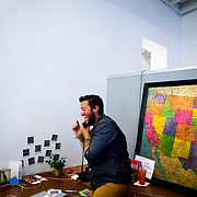 Roadie Tyler Karr, 23, records an out-of-office message before heading off on tour at Invisible Children headquarters on Monday, Sept. 16, 2013 in San Diego, Calif.