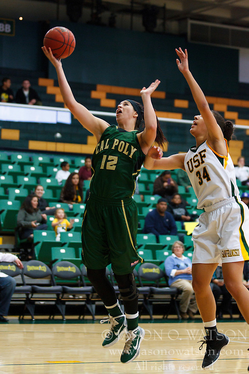 Nov 16, 2011; San Francisco CA, USA;  Cal Poly Mustangs forward Kristina Santiago (12) shoots past San Francisco Lady Dons forward Whitney Daniels (34) before the game at War Memorial Gym.  Mandatory Credit: Jason O. Watson-US PRESSWIRE