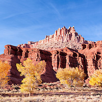 Rock formation, The Castle, in Capitol Reef National Park, with cottonwood trees adorned with golden colors of fall. Near Torrey, Utah.