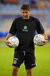 PODGORICA, MONTENEGRO - Wednesday, August 12, 2009: Wales' assistant coach Dean Saunders warms-up wearing a shirt in support of former captain John Hartson who is battling against cancer, and to promote awareness of men's health issues with web site checkemlads.com, before an international friendly match against Montenegro at the Gradski Stadion. (Photo by David Rawcliffe/Propaganda)