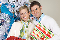 Couple holding presents by Christmas tree, portrait