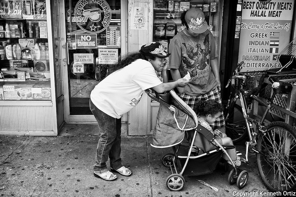 A mother makes a call as her kids wait on 30th Avenue in Astoria Queens.