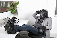 Thoughtful young man in gorilla costume resting at office