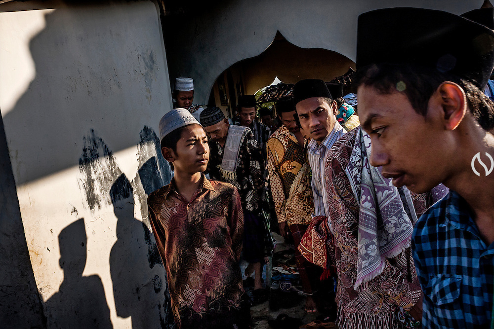 Muslim villagers leave the mosque after a pray.