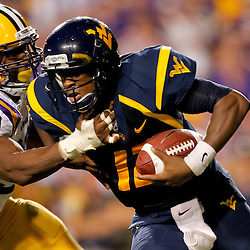 Sep 25, 2010; Baton Rouge, LA, USA; LSU Tigers defensive end Sam Montgomery (99) tackles West Virginia Mountaineers quarterback Geno Smith (12) during the second half at Tiger Stadium. LSU defeated West Virginia 20-14.  Mandatory Credit: Derick E. Hingle