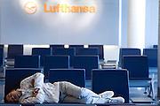 Frankfurt am Main | 18.04.2010..Durch den Ausbruch des Vulkans Eyjafjallajoekull auf Island und dadurch ausgestossene Aschewolken ist der Luftraum ueber weiten Teilen Europas f?r den Flugverkehr gesperrt, dadurch sitzen im Transit-Bereich im Flughafen Frankfurt etwa 800 Menschen fest, die kein Visum f?r Deutschland haben. Hier: Ein Reisender schlaeft auf einer Sitzreihe unter einem Logo der Lufthansa. ..Foto: peter-juelich.com..[No Model Release | No Property Release]