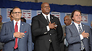 COOPERSTOWN, NY - JULY 27:  2014 Baseball Hall of Famer inductees Joe Torre (L), Frank Thomas and Tony LaRussa pause during the National Anthem during the 2014 induction ceremonies held at the Clark Sports Center in Cooperstown, New York on July 27 2014.