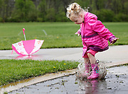 Madeleine Gill, 3, whose favorite color is pink, dropped her umbrella while testing out her new rain boots and jacket by splashing around in puddles at the Westerville Sports Complex on April 30, 2014. Gill's mother, Erin Gill, said they recently moved to Westerville because of its park system, in which they planned on playing all afternoon, even in the rain.