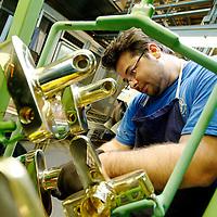 DEU , DEUTSCHLAND : Produktion von Badarmaturen bei der Grohe GmbH in Hemer : nach der Oberflaechenkontrolle steckt ein Mitarbeiter ein Armaturengehaeuse auf ein Galvanikgestell.  DEU , GERMANY : Production of bathroom fittings at Grohe GmbH in Hemer : after inspecting the surface a worker puts an armature body onto a rack ..  24.07.2012. Copyright by : Rainer UNKEL , Tel.: 0171/5457756