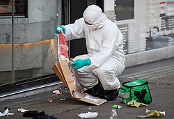 © Licensed to London News Pictures. 17/02/2019. London, UK. A police forensics officer places blood covered items in an evidence bag at the scene on Oxford Street in central London where three people were stabbed last night. The incident took place near Tape Nightclub. Photo credit: Ben Cawthra/LNP
