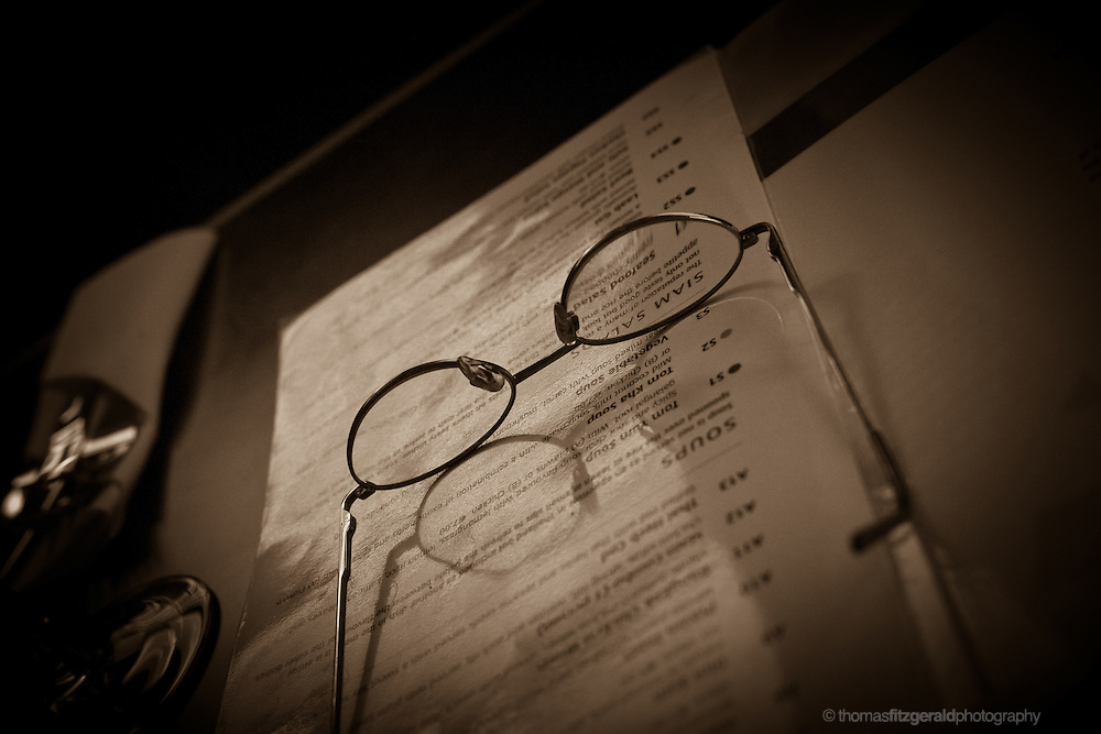 A set of reading glasses rest on a menu while waiting for food to arrive