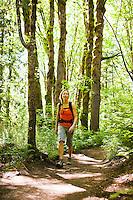A woman walkinga trail in the forest, Little Si trail, Washington, USA.