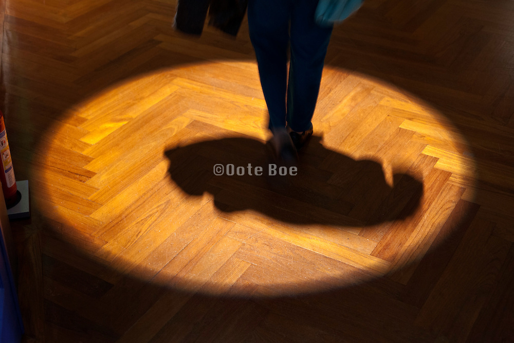 parquet floor with spotlight and person walking