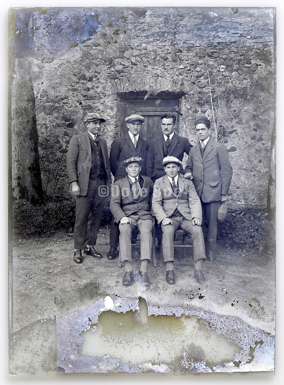 eroding glass plate with adult male group posing