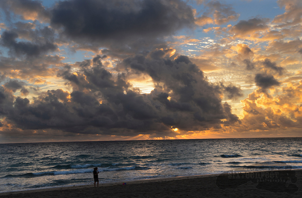 Photo by Gary Cosby Jr.  A man walks along the beach at sunrise in Ft. Lauderdale, Florida.