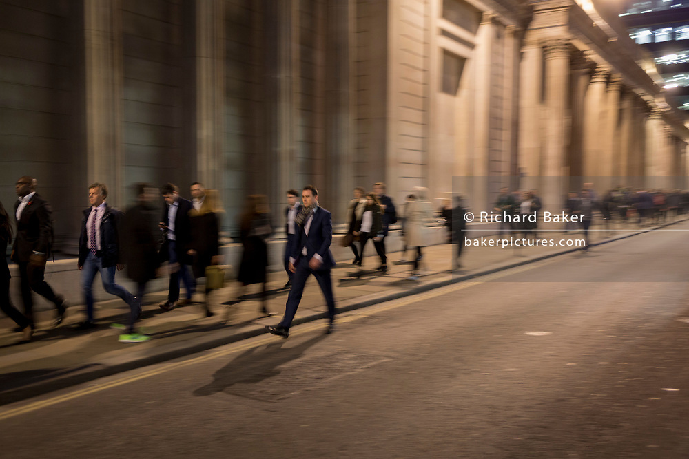 Blurred commuters walk along Threadneedle Street, below the walls and columns of the Bank of England in the heart of the Square Mile, the capital's historical and financial centre, on 1st November 2017, in the City of London, England.
