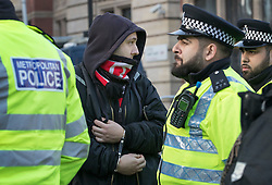 © Licensed to London News Pictures. 05/12/2016. London, UK. Police detain a man (in handcuffs) involved in a scuffle between pro and anti Brexit groups outside the Supreme Court in Westminster, London on the first day of a Supreme Court hearing to appeal against a November 3 High Court ruling that Article 50 cannot be triggered without a vote in Parliament. Photo credit: Peter Macdiarmid/LNP