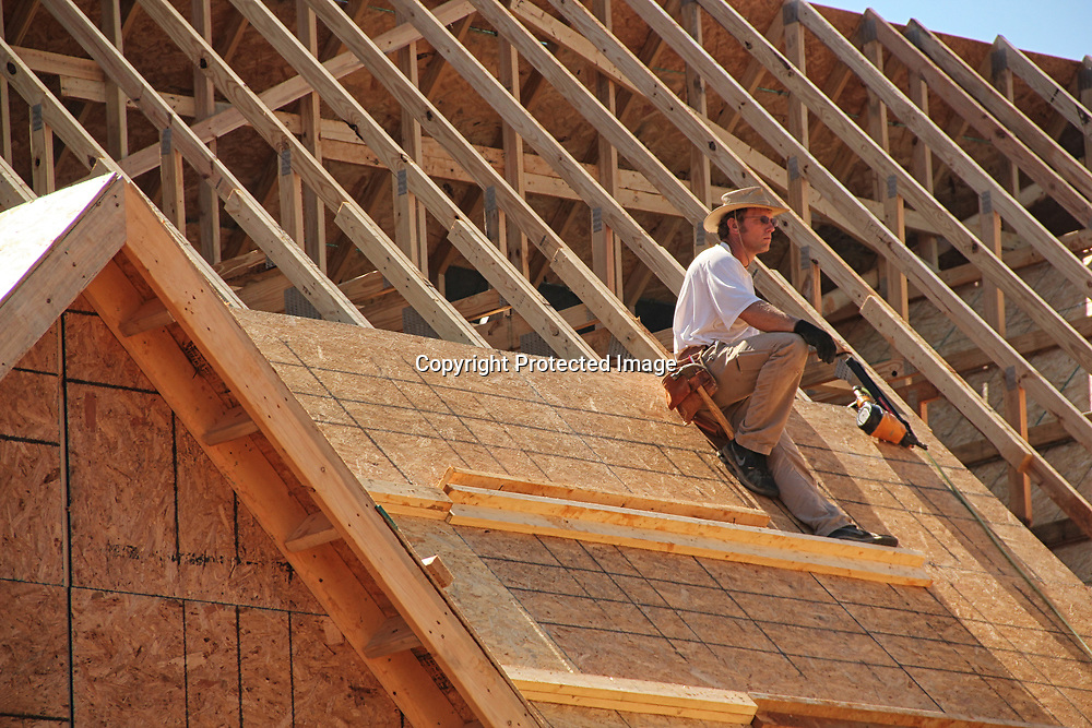 A worker takes a break on the partially constructed roof of the Crossroads lodge.