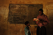 Bea Ahbeck/Fremont Argus 10/25/05<br /> <br /> Alex Zinga, 8, watches as his primary 1 teacher Geofrey Lubowa looks over his work duirng class at the Future Victory School  in the Kamuli District, Uganda, Oct. 25, 2005. 60% of the school's students are HIV/AIDS orphans, many of them HIV positive themselves.