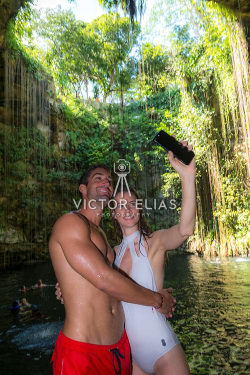 Couple taking selfie at Cenote Ik-Kil