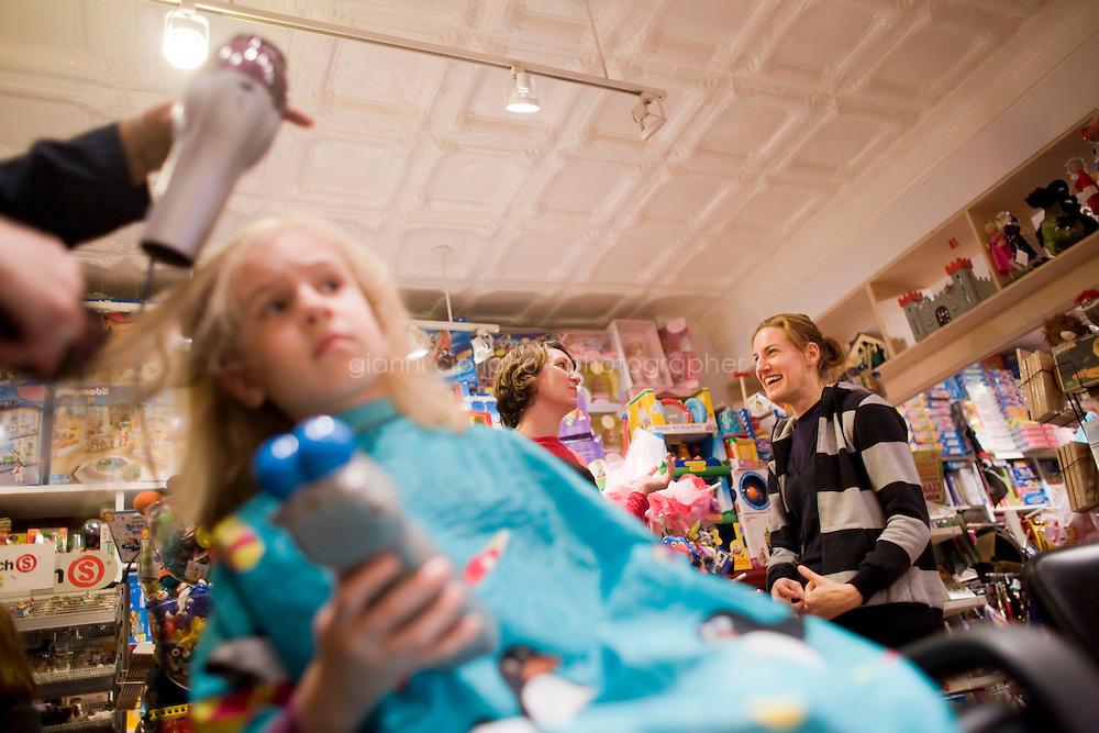 """7 Novembre, 2008. Brooklyn, New York.<br /> <br /> Chiara Cecchini (sinistra) , 5 anni, si fa tagliare i capelli al Lulu's Cuts & Toys, una parruccheria per bambini e negozio di giocattoli a Park Slop, Brooklyn, NY. Nello sfondo, a destra,  è presente la madre, Jessica Cecchini. Park Slope, spesso definito dai newyorkesi come """"The Slope"""", è un quartiere nella zona ovest di Brooklyn, New York, e confinante con Prospect Park.  Park Slope è un quartiere benestante che ha il maggior numero di nascite, la qualità della vita più alta e principalmente abitato da una classe media di razza bianca. Per questi motivi molte giovani coppie e famiglie decidono di trasferirsi dalle altre municipalità di New York a Park Slope. Dal punto di vista architettonico, il quartiere è caratterizzato dai brownstones, un tipo di costruzione molto frequente a New York, e da Prospect Park.<br /> <br /> ©2008 Gianni Cipriano for The New York Times<br /> cell. +1 646 465 2168 (USA)<br /> cell. +1 328 567 7923 (Italy)<br /> gianni@giannicipriano.com<br /> www.giannicipriano.com, 5 anni, si fa tagliare i capelli al Lulu's Cuts & Toys, una parruccheria per bambini e negozio di giocattoli a Park Slop, Brooklyn, NY. Park Slope, spesso definito dai newyorkesi come """"The Slope"""", è un quartiere nella zona ovest di Brooklyn, New York, e confinante con Prospect Park.  Park Slope è un quartiere benestante che ha il maggior numero di nascite, la qualità della vita più alta e principalmente abitato da una classe media di razza bianca. Per questi motivi molte giovani coppie e famiglie decidono di trasferirsi dalle altre municipalità di New York a Park Slope. Dal punto di vista architettonico, il quartiere è caratterizzato dai brownstones, un tipo di costruzione molto frequente a New York, e da Prospect Park.<br /> <br /> ©2008 Gianni Cipriano for The New York Times<br /> cell. +1 646 465 2168 (USA)<br /> cell. +1 328 567 7923 (Italy)<br /> gianni@giannicipriano.com<br /> www.giannicipriano.com"""