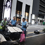 Street cleaners at work in Central. One of the workers shares a can of coke he has found. The streets of Hong Kong are kept clean by an army of street cleaners, many elderly men and women.<br />