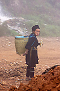 Hilltribe villages around Sapa. Black Hmong woman carrying a basket on her back.