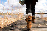 Annandale Way,  Lochmaben, shot of young woman's legs wearing black tights, black knee-high socks and beige boots walking on boardwalk next to the water on a hazy day. There are long golden grasses next to the boardwalk and land in the distance.