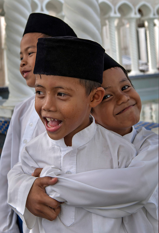 Moslem boys  wait to attend friday prayers at the Omar Ali Saifuddien Mosque..Bandar Seri Begawan, Brunei.