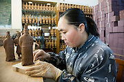 Woman makes Terracotta Warrior souvenirs in factory, Xian, China