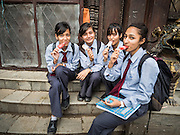 30 JULY 2015 - KATHMANDU, NEPAL:    Nepalese school girls eat ice cream treats in the courtyard at Shree Gha stupa, a large Buddhist stupa near Durbar Square in Kathmandu.   PHOTO BY JACK KURTZ