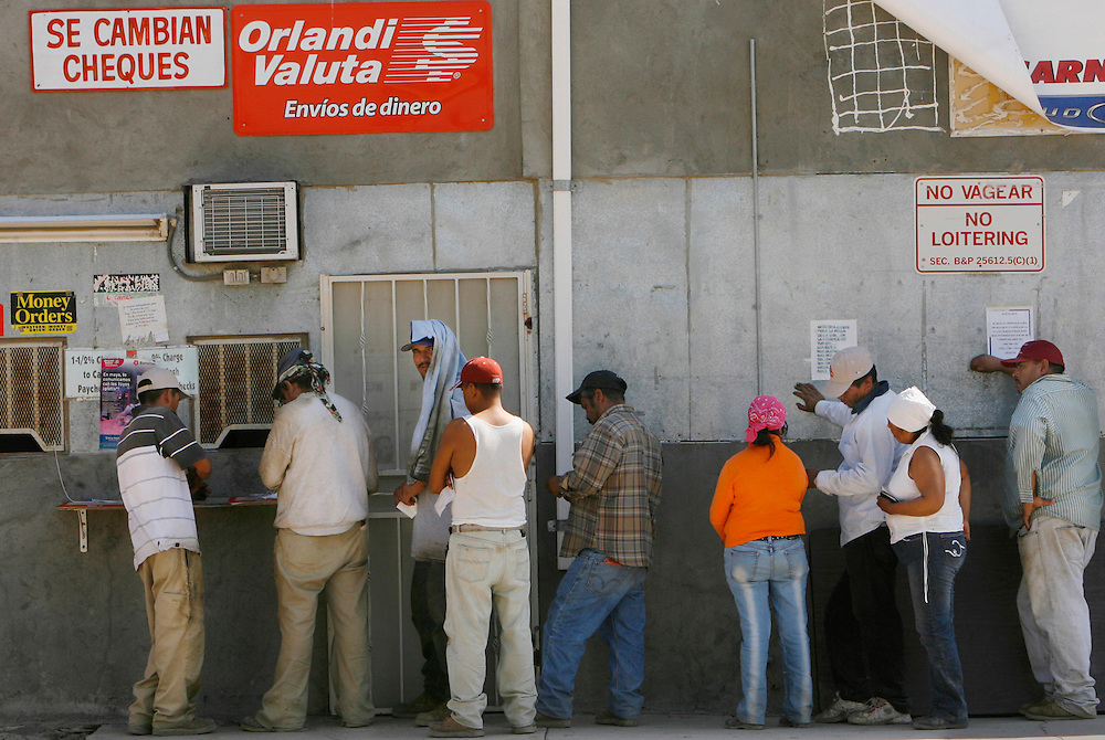 Mecca for Misery.Farm workers line up to cash their checks in Mecca, Ca. Most workers earn between 7-9 dollars per hour for picking grapes in triple digit temperatures. Many workers try to be frugal so they can send some money  back to their families in Mexico.
