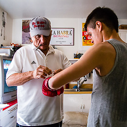 A boxer gets his gloves tied on by his coach in a quiet moment before practice at La Habra Boxing Club in La Habra, CA. (Chris Mast/Christopher Mast Images)