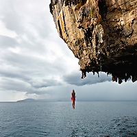 """Thai climber """"deep water soloing"""" without rope, returns to earth, Poda Island, Krabi, Thailand"""