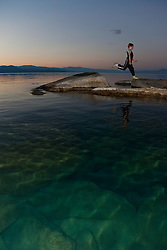 """Boy at Lake Tahoe 6"" - This boy was photographed near Speedboat Beach, Lake Tahoe,  jumping from rock to rock at sunrise."