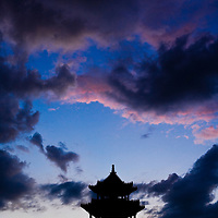 The twilight sunset silhouettes a pagoda with two people at a new temple park in the city of Bayan Ul Hot, Inner Mongolia, China.