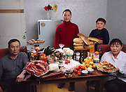 (MODEL RELEASED IMAGE).The Batsuuri family in their single-room home (a sublet in a bigger apartment) in Ulaanbaatar, Mongolia, with a week's worth of food. Standing behind Regzen Batsuuri, 44 (left), and Oyuntsetseg (Oyuna) Lhakamsuren, 38, are their children, Khorloo, 17, and Batbileg, 13. The Batsuuri family is one of the thirty families featured in the book Hungry Planet: What the World Eats (p. 226).