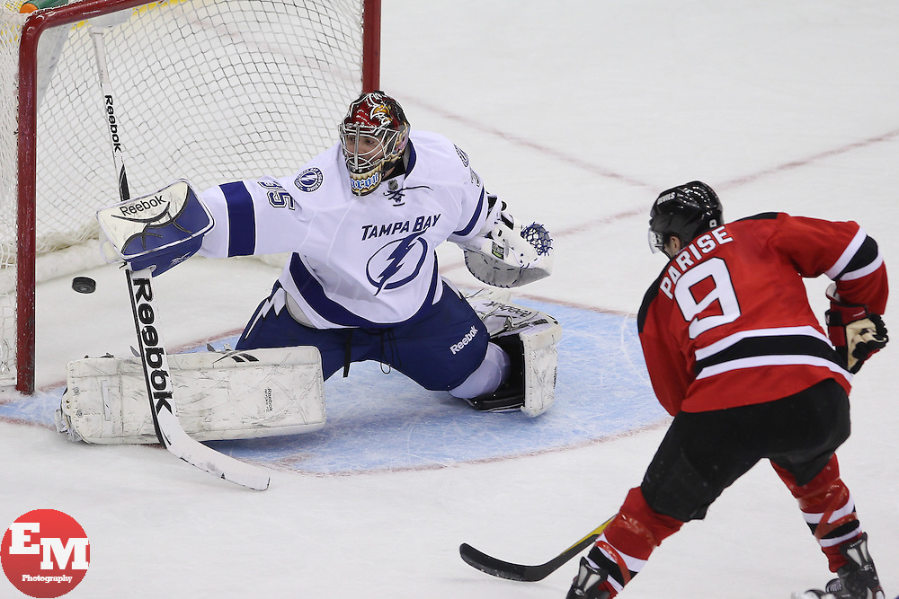Mar 29; Newark, NJ, USA; Tampa Bay Lightning goalie Sebastien Caron (35) makes a save on New Jersey Devils left wing Zach Parise (9) during the third period at the Prudential Center. The Devils defeated the Lightning 6-4.